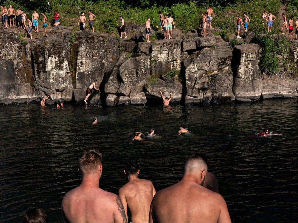 Cliff divers line up along the Clackamas River at High Rocks Park at on June 27, 2021 in Portland, Oregon