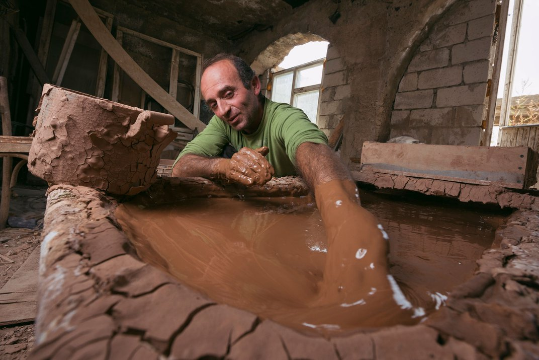 A man in a green shirt reaches in to a pool of clay, prepared for work.