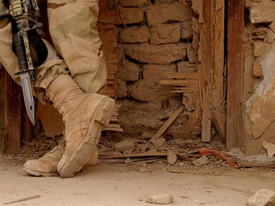 A member of the U.S. Army 3/187th Scouts from Fort Campbell, Kentucky, takes a break at a bombed out building on April 12, 2002, at Kandahar Air Base, Afghanistan.