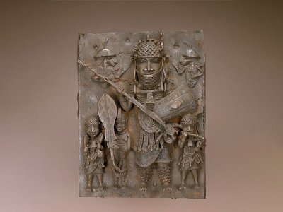 This plaque depicts musicians, a page holding a ceremonial sword and a high-ranking warrior. It numbers among the thousands of works looted by British forces during an 1897 raid of Benin City.