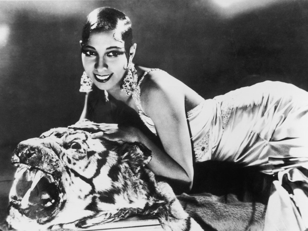 Josephine Baker lying on a tiger rug in a silk evening gown in 1925