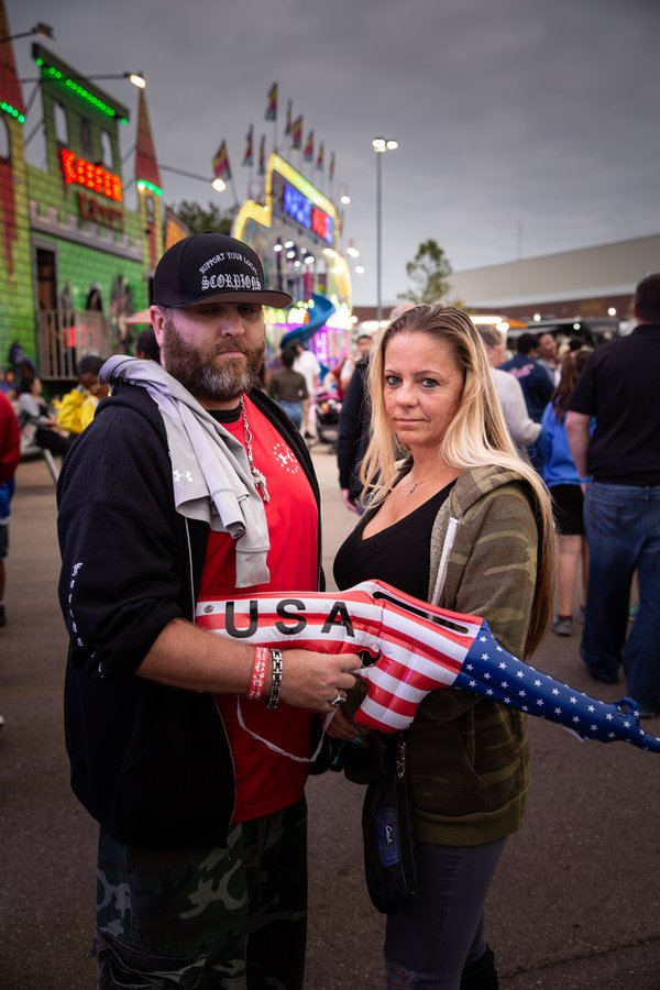 A couple holds a blow-up gun at the Michigan State Fair. thumbnail