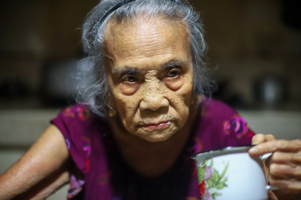 91-year-old grandmother sits at the dining table and stares with glaring eyes thumbnail