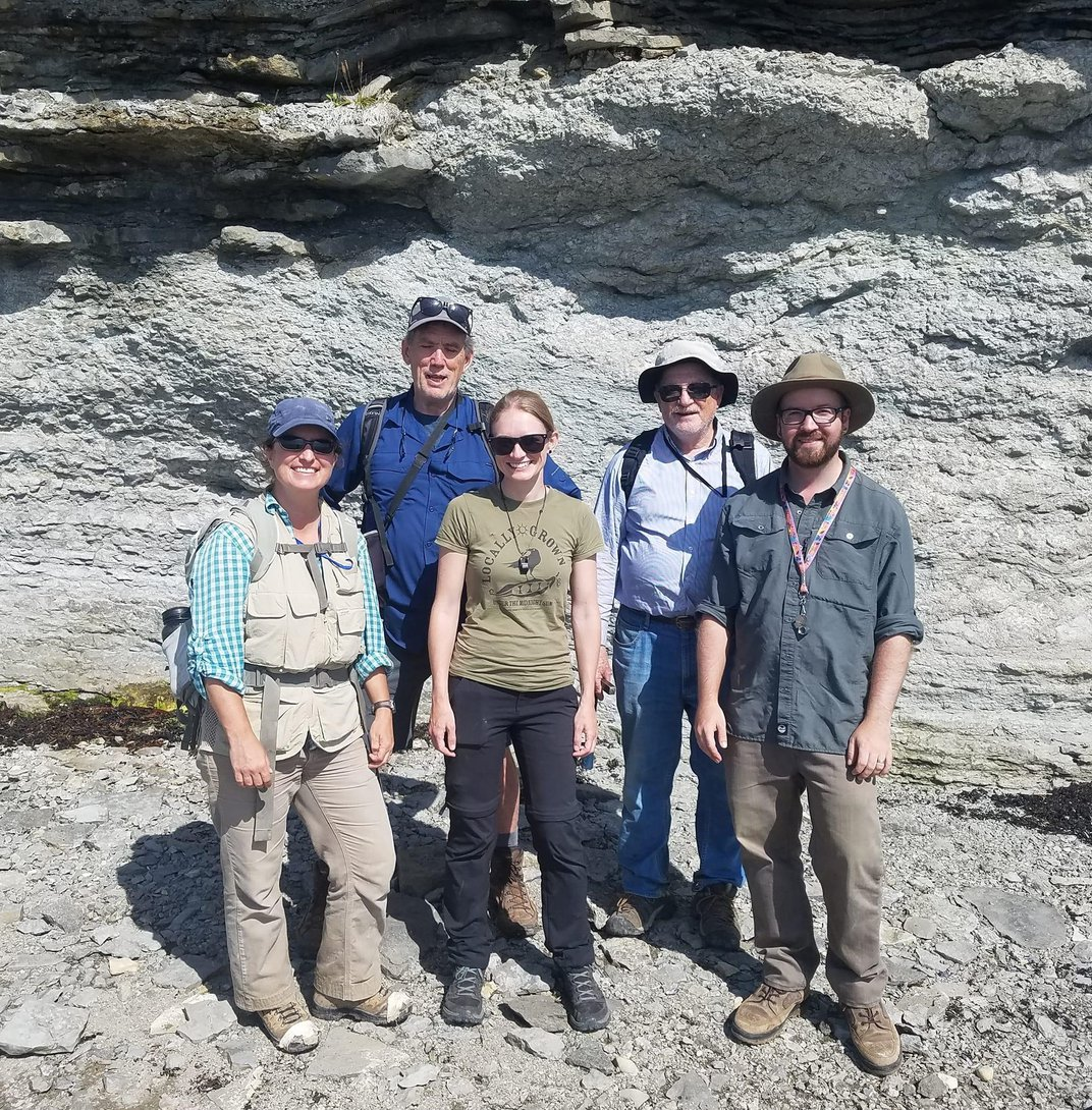 A group of people in front of a rocky cliff.