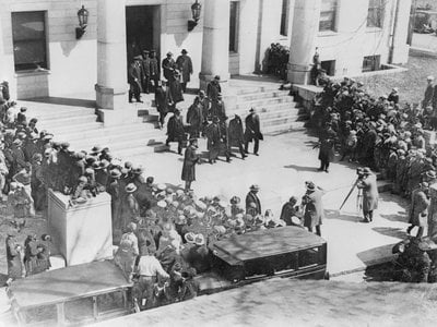 Nicola Sacco and Bartolomeo Vanzetti leave jail at Dedham, Mass., en route to the courthouse where they are to be sentenced by Judge Webster Thayer to die in the electric chair.