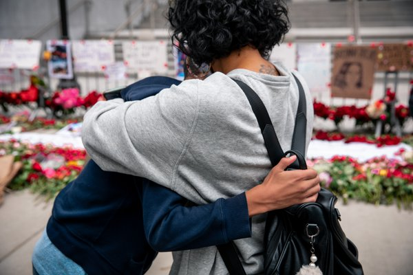 Mother and son hug in front of a BLM monument thumbnail
