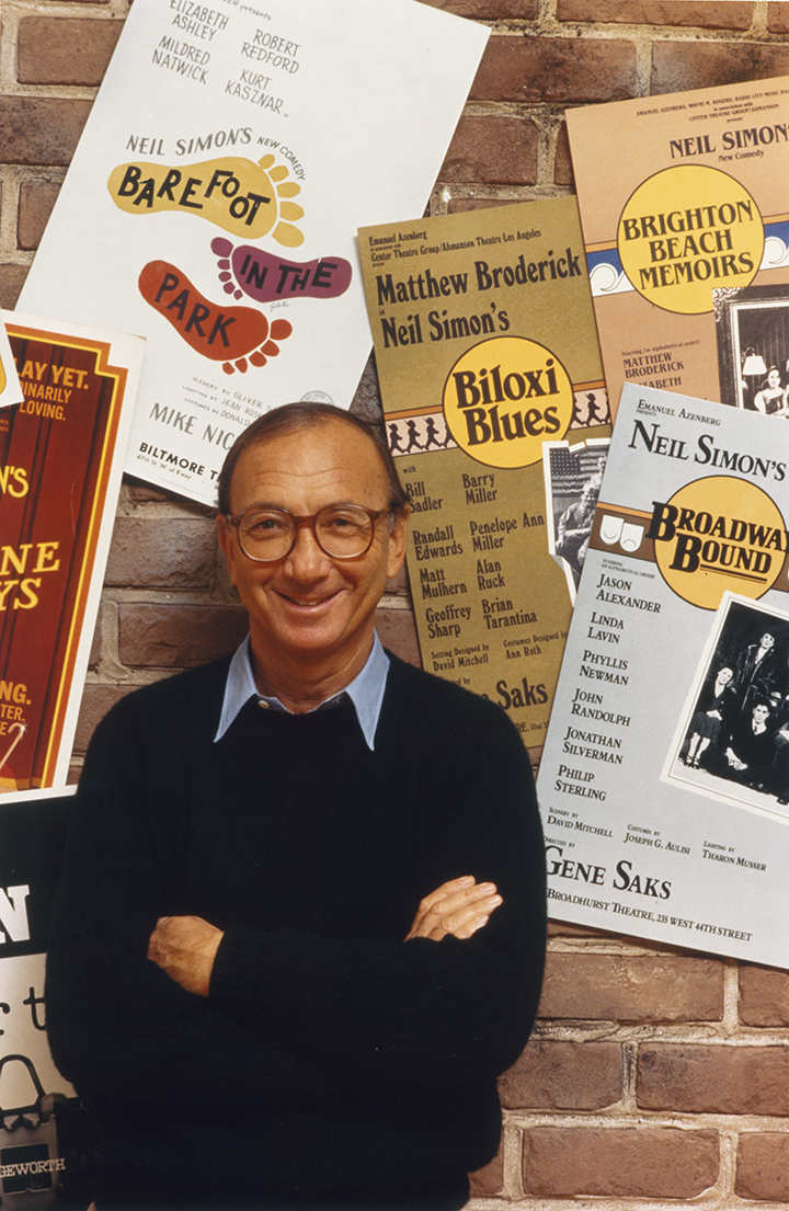 Neil Simon stands with arms crossed, smiling against a brick wall covered in posters