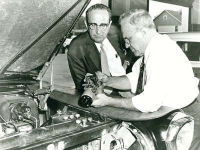 Ralph Teetor (right), cruise control in hand, with William Prossner, president of Perfect Circle, in 1957.