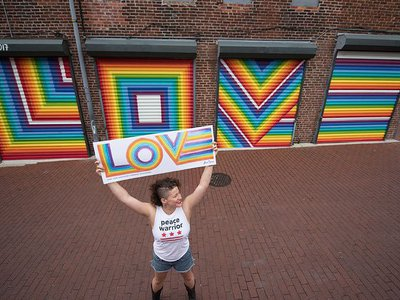 Lisa Marie Thalhammer holds her original LOVE poster with her mural in the background.