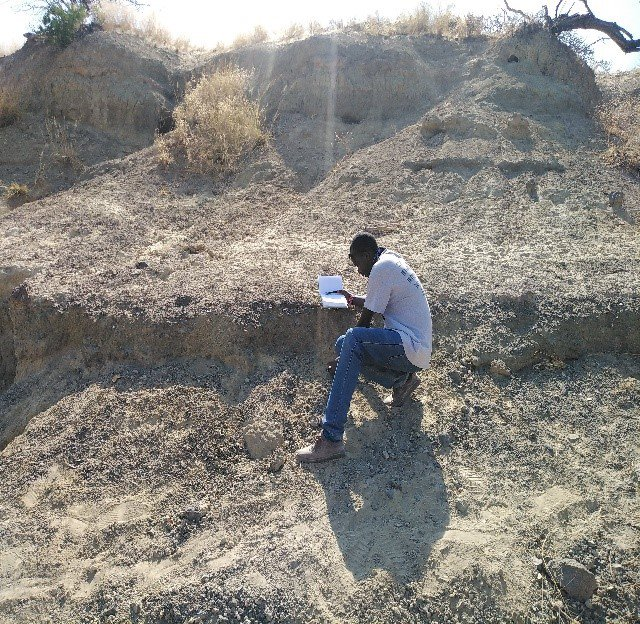 Sylvester Musembi Musyoka, a Kenyan colleague and field crew leader, recording a large mammal fossil bone during a virtual field project to collect fossils in Kenyan excavation sites that were in danger of being damaged by severe weather. (Nzioki Mativo/Smithsonian)