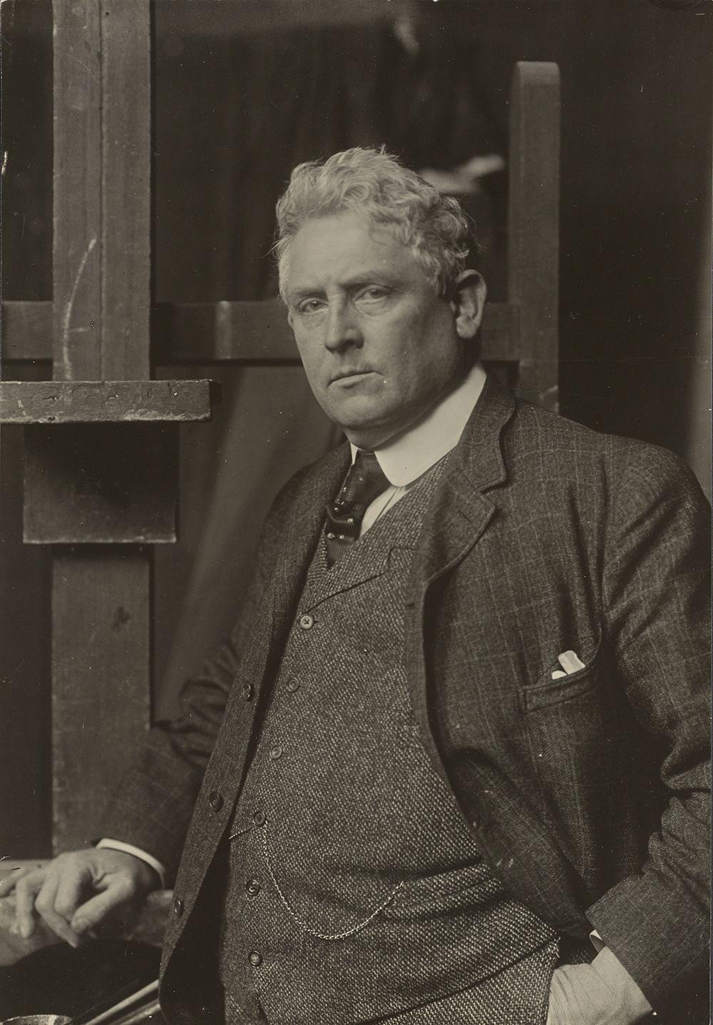 Julian Alden Weir in his studio wearing a suit and tie in a formal portrait.