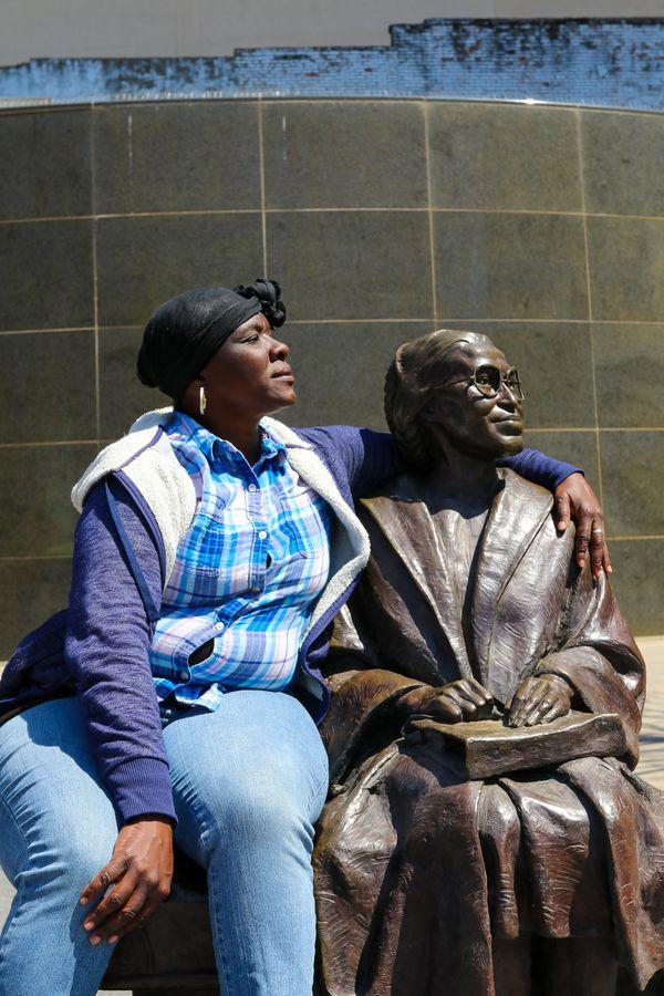 Homeless Woman Hugging Rosa Parks Statue thumbnail