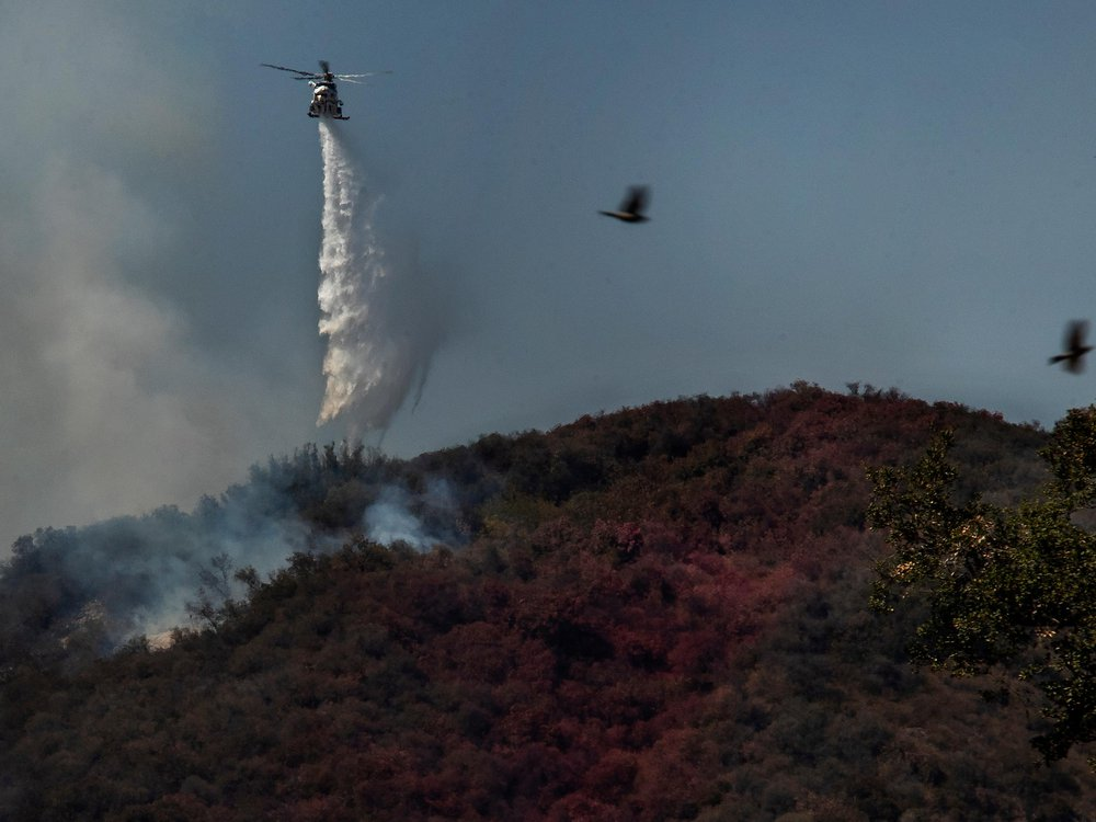 Firefighters in helicopters battle a 1,300 acre brush fire in Pacific Palisades on May 17.