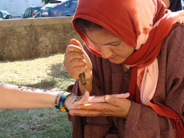 Moroccan woman applies henna to a tourist's arm. thumbnail