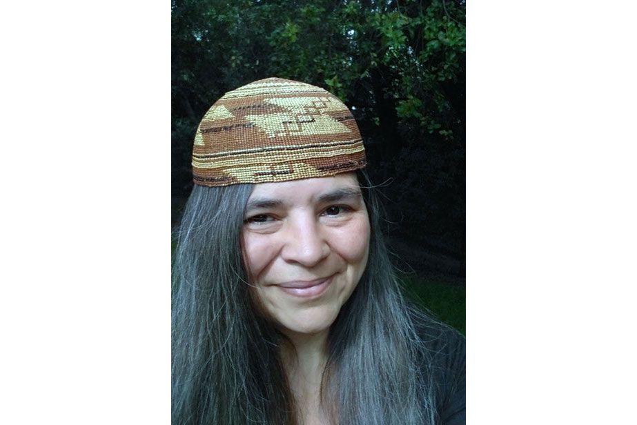 Selfie portrait of a woman with long dark hair, wearing a woven basket cap with geometric pattern.