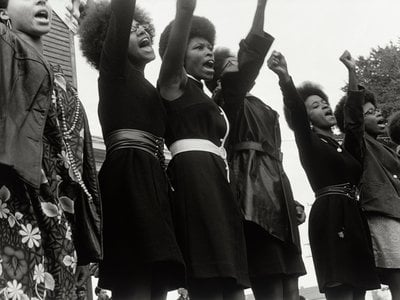 A photo taken at a Free Huey Newton Rally in 1968 with five of the six women identifiable—Delores Henderson, Joyce Lee, Mary Ann Carlton, Joyce Means and Paula Hill—provides testament to those who actualized the daily operations of the Black Panther Party.