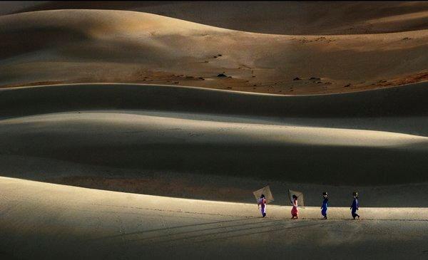 When the sunset, some of women come back home passing the sand dune thumbnail