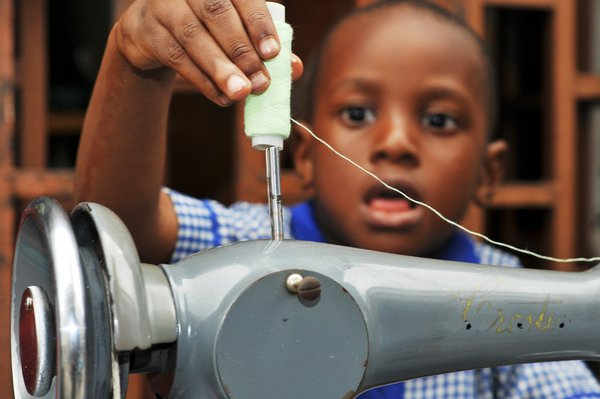 Boy playing with a sewing machine at a local shop after school thumbnail