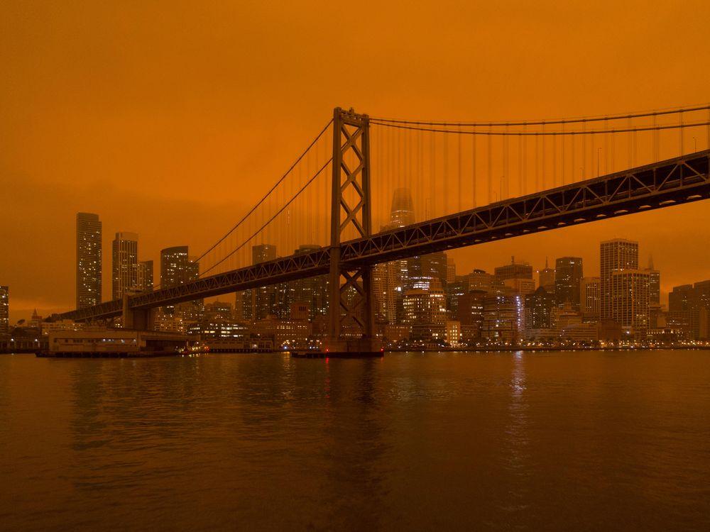 The Golden Gate Bridge and San Francisco skyline with a background of hazy, dark orange sky.