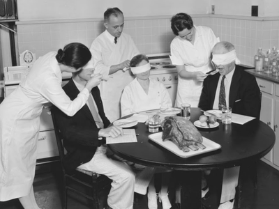 Bureau of Home Economics employees blindfold their taste testers so the sight of the turkey doesn't bias any responses, 1930s.
