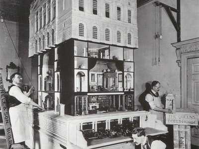 Workers furnish Queen Mary's Dollhouse in the drawing room of Lutyen's London apartment
