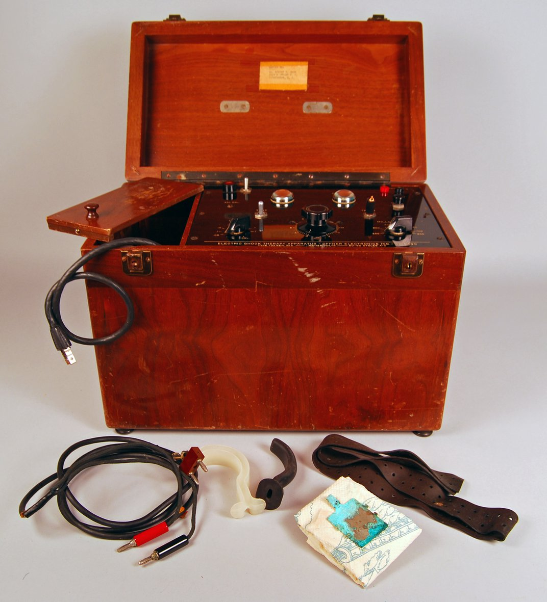 Red wooden electroshock machine with wires and other accessories