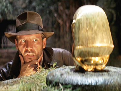 Harrison Ford as Indiana Jones, sizing up the idol, in the opening scene of Raiders of the Lost Ark
