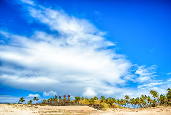 Moai on a beach on Easter Island, with palm trees and dramatic skies thumbnail