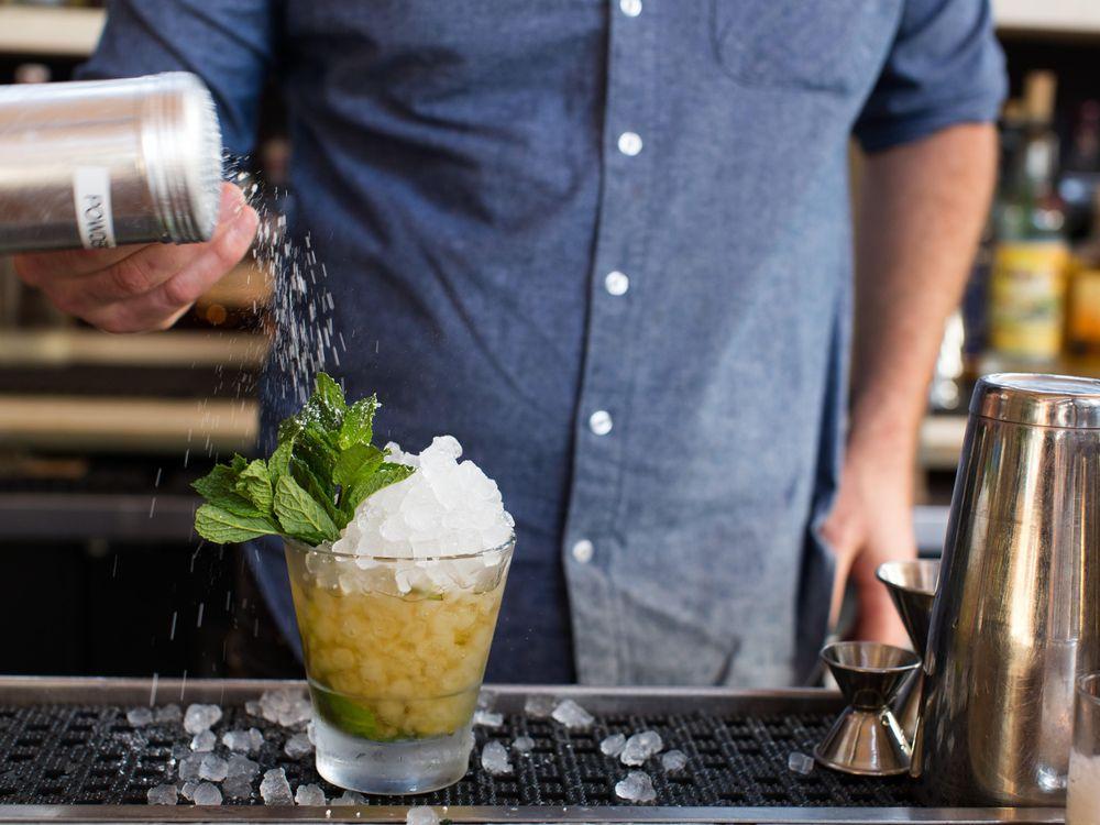Bartender making mint julep cocktail
