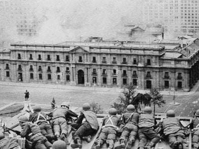 Soldiers supporting the coup led by Gen. Augusto Pinochet take cover as bombs are dropped on the Presidential Palace of La Moneda in Sept. 11, 1973.