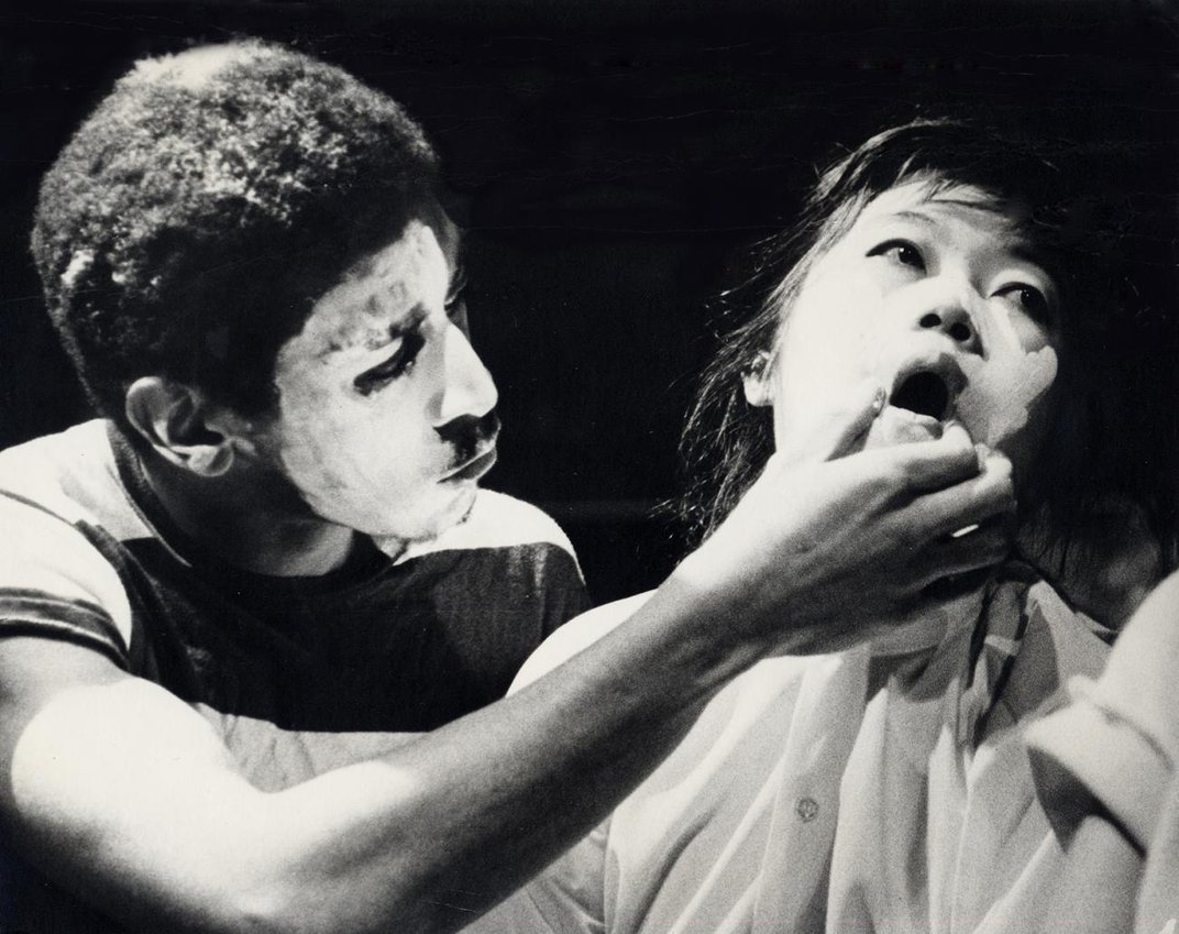 A film still of a man holding a woman's mouth.