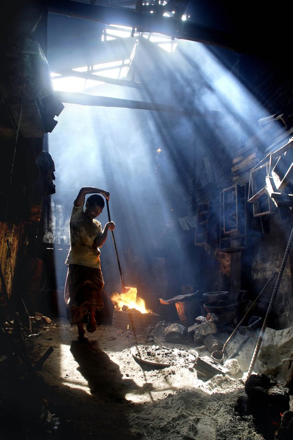 A man working at a cast-iron workshop, in Khulna city, in Bangladesh. July 26, 2008. thumbnail