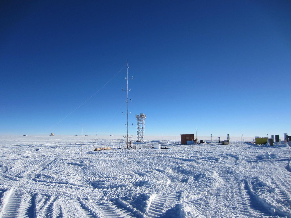 A view of Dome A site during daytime: a large expanse of snow, blue sky, and two metal structures rise out of the ground