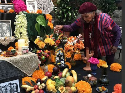 """Doña Ofelia Esparza decorates the ofrenda """"Sacred Connections,"""" created with her daughter Rosanna Esparza Ahrens for the 2019 celebration of El Día de los Muertos—the Day of the Dead—at the National Museum of the American Indian in Washington."""