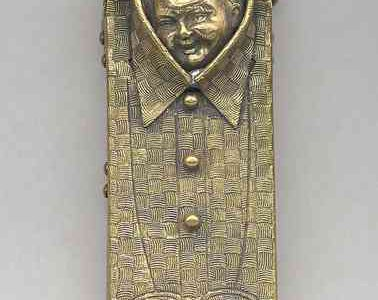 """Matchbook in the shape of a folded men's shirt, with incised checkerboard-patterned weave, cuffs and bib, smiling child's head peering out from opening at collar. Reverse inscribed """"New York Clothing House, 102 & 104 Baltimore St., Baltimore."""" Upper curved section swings open to reveal match compartment,  c. mid-19th century."""