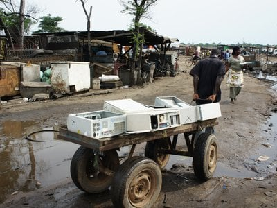 A man pulls a cart full of empty PC cases that'll be broken down by recyclers in Agbogbloshie, in Accra, Ghana.