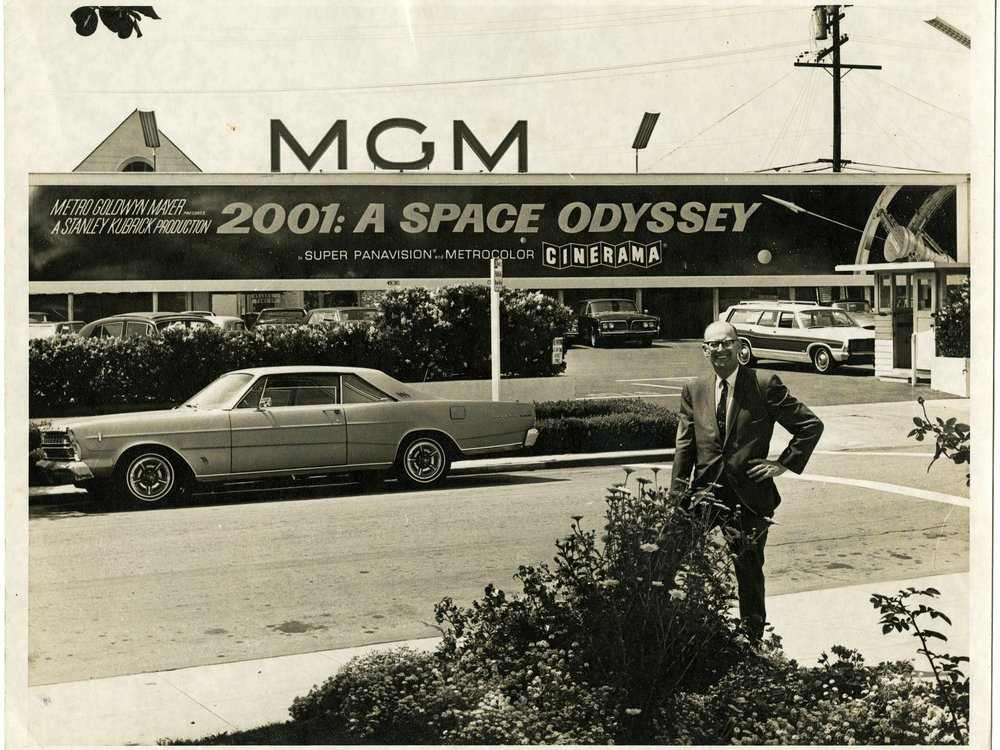 Arthur C. Clarke poses for a photo beneath a sign advertising the motion picture