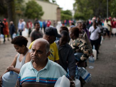 Residents queue to fill containers with water from a source of natural spring water in Cape Town, South Africa, Friday, Feb. 2, 2018.
