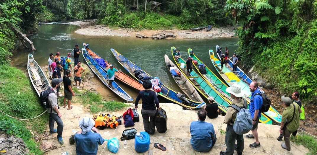 The researchers and their guides loaded kayak-like boats with supplies on the side of a river before venturing to the field site in the Malaysian state of Sarawak.