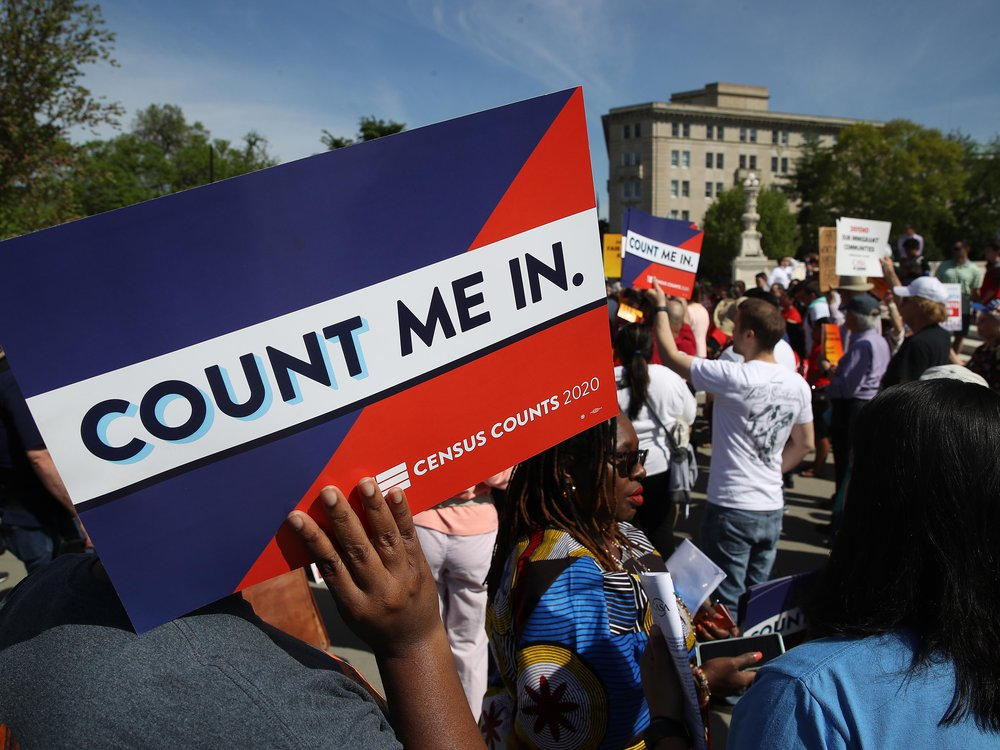 """A protestor holds a sign that says """"Count Me In"""""""