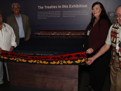 """Delaware leaders prepare to unveil the Treaty of Fort Pitt, on view at the National Museum of the American Indian in Washington, D.C. From left to right: Denise Stonefish, chief of the Delaware Nation at Moraviantown; museum director Kevin Gover; Chester """"Chet' Brooks, chief of the Delaware Tribe of Indians; and Deborah Dotson, president of the Delaware Nation. May 10, 2018, Washington, D.C. (Paul Morigi/AP Images for the National Museum of the American Indian, Smithsonian)"""