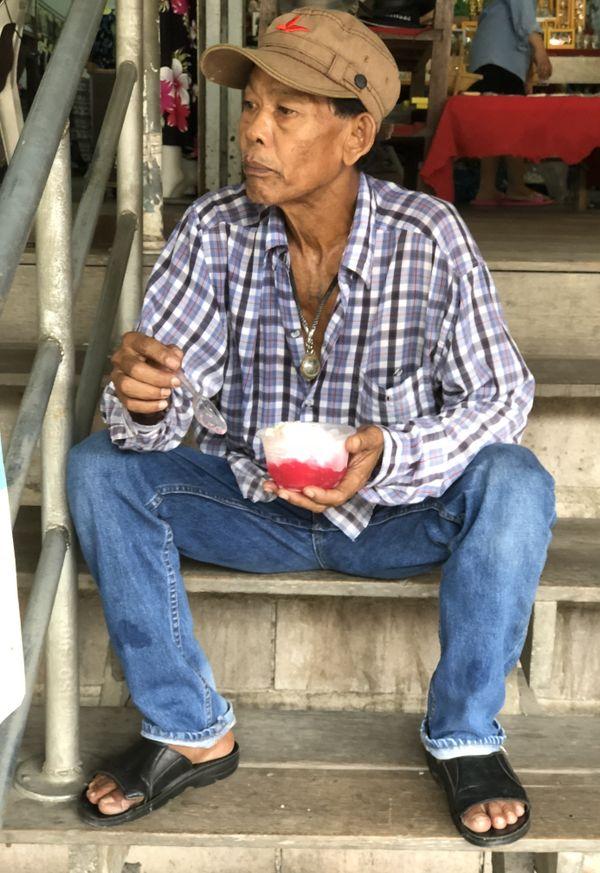 Man eating ice cream on a hot day outside of Bangkok thumbnail