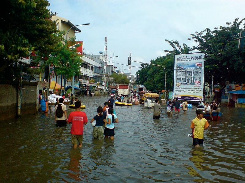 A view of a flooded marketplace in Jakarta. People are wading through knee-high water in the middle of a street. It looks like a typical, bustling street except that the street is entirely flooded.