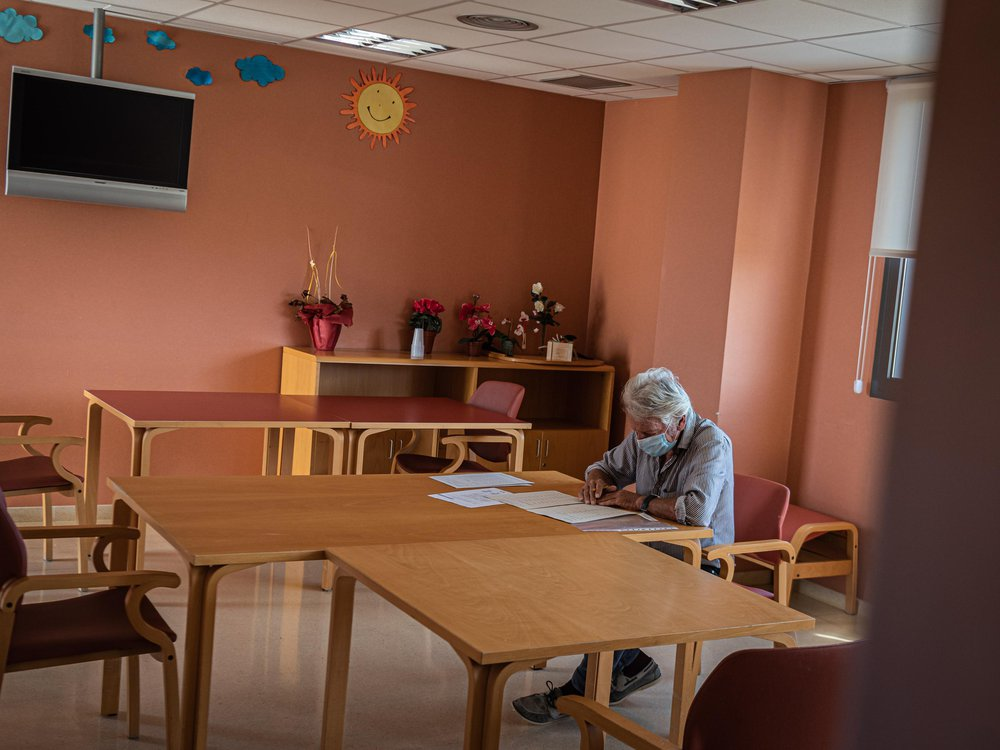 A person sits at a table wearing a mask and writing. The room in the nursing home is otherwise empty and has coral-colored walls