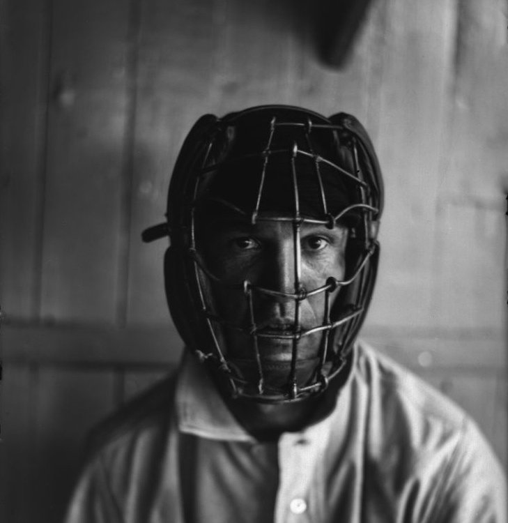 A player wearing an old-fashioned catcher's mask