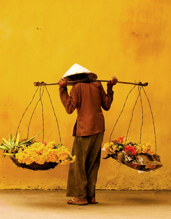 A Vietnamese woman selling flowers on the streets of Hoi An, Vietnam. thumbnail
