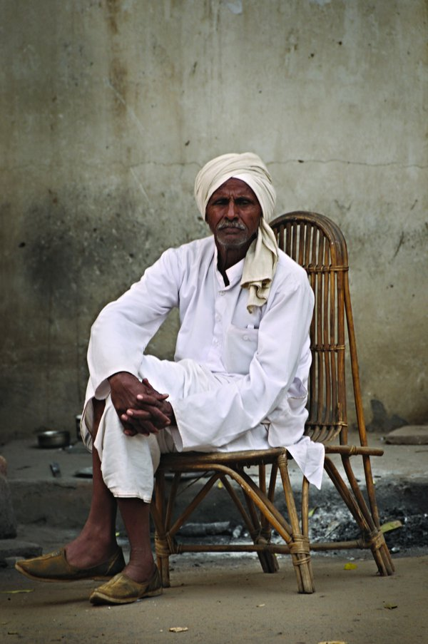 Dignity is not about wealth. Man resting on his chair at a street in Delhi thumbnail
