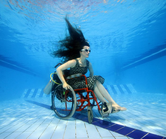Artist Sue Austin scopes out a pool in her underwater wheel chair.
