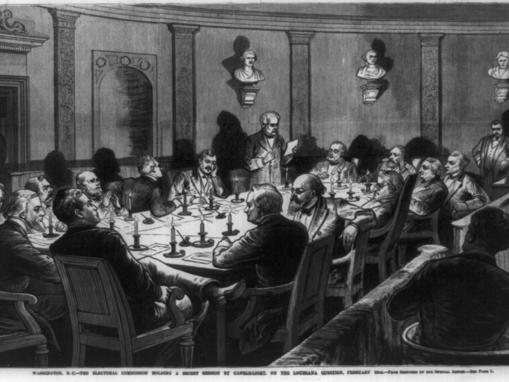 A black and white depiction of a group of men, sitting at a table in a formal room illuminated by candlelight on the table