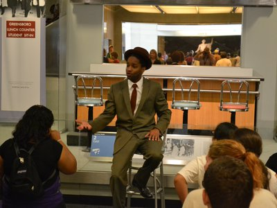 """Among the ways that the American History Museum has engaged visitors was the 2010 interactive play """"Join the Student Sit-Ins,"""" starring actor Xavier Carnegie (above) at one of the iconic objects in the Smithsonian's collection, the Greensboro Lunch Counter, where on February 1,1960, four Black college students at North Carolina A & T University began a legendary sit-in for racial justice."""